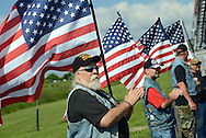 "WARMINSTER, PA - JUNE 14: Paul ""Dutch"" Rievley of Warriors Watch Riders holds an American flag along with members of his group at the finish line during the Wounded Hero 5K to support the Honor & Courage Program of Operation Ward 57 June 14, 2014 at Warminster Community Park in Warminster, Pennsylvania. The event is created to show support for our nation's wounded heroes. (Photo by William Thomas Cain/Cain Images)"