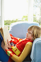 Young boy (7-9) sitting in armchair reading wearing superhero costume side view