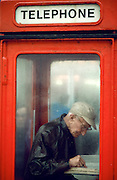 Man in red telephone booth, Blackpool, England