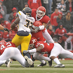 Dec 5, 2009; Piscataway, NJ, USA; West Virginia running back Ryan Clarke (32) is gang-tackled by Rutgers defenders during first half NCAA Big East college football action between Rutgers and West Virginia at Rutgers Stadium.
