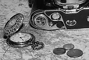 old style pocket watch, camera and coins on a map in black and white