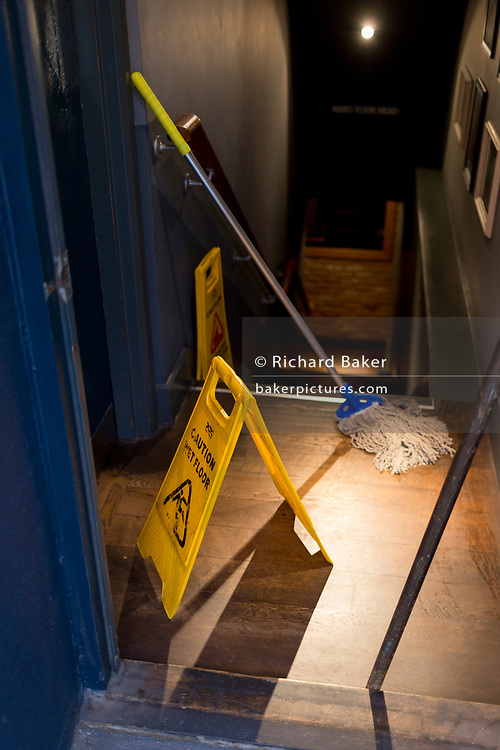 A caution sign for a wet floor, after the cleaning of the entrance and stairs of a Westminster pub on Charlotte Street, on 16th January 2019, in London, England.
