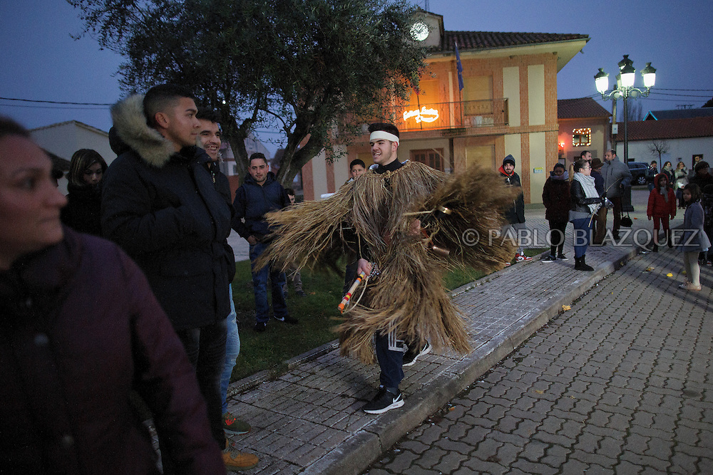 A man dressed as El Tafarron hits a reveller during El Tafarron festival on December 26, 2016 in Pozuelo de Tabara, Zamora province, Spain.  El tafarron is a pagan winter masquerade that takes place during Saint Esteban festivities. The festival is represented by El Tafarron and La Madama. El wears a custome of straw and a mask. (© Pablo Blazquez)