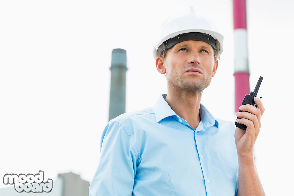 Male architect holding walkie-talkie at site