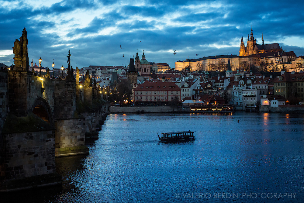 A boat on Vltava river at dusk, charles Bridge on the left, Prague castle on the back.