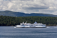 The BC Ferries ship Spriit of British Columbia (built in 1993) navigates Trincomali Channel on the way to Victoria (Swartz Bay) from Tsawwassen.  Photographed from Village Bay on Mayne Island, British Columbia, Canada.  Island in the background is Prevost Island (front) and Salt Spring Island behind.