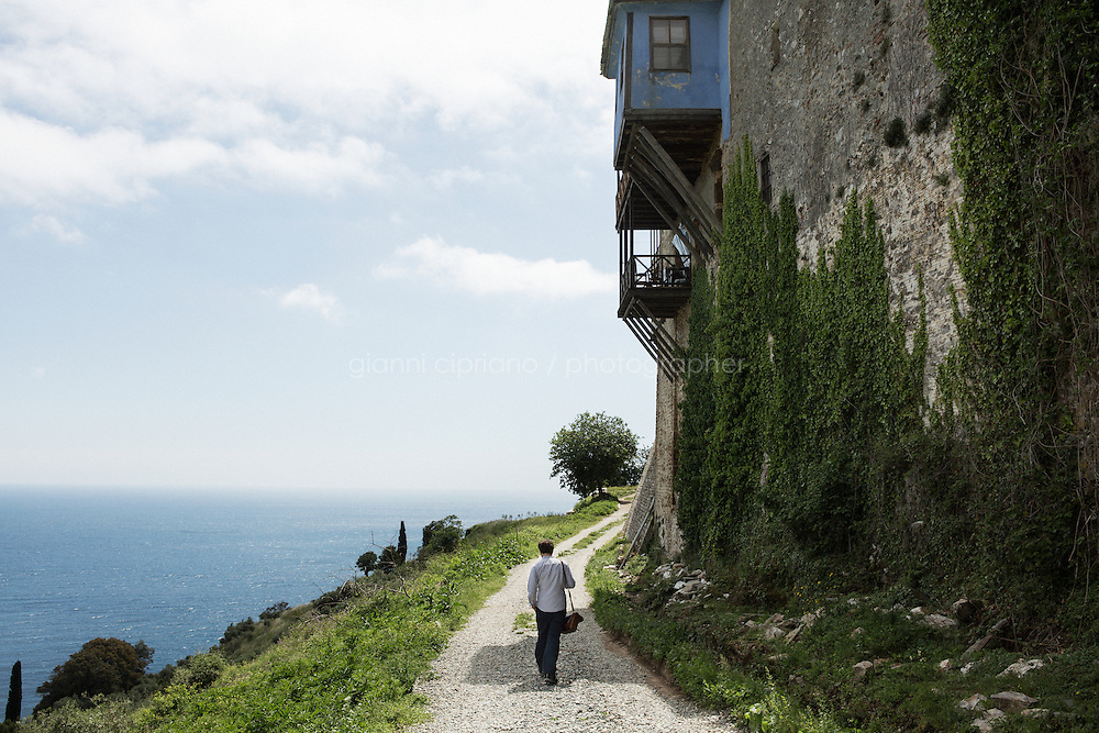 MOUNT ATHOS, GREECE - 8 MAY 2014: Writer Max Scharnigg walks along the perimeter of Great Lavra, the oldest monastery of Mount Athos, Greece, on May 8th 2014.<br /> <br /> Great Lavra (Megistis Lavra) was founded in 963 by Athanasius the Athonite and marks the beginning of the organized monastic life at Mount Athos.<br /> <br /> Mount Athos is a mountain and peninsula in Greece. A World Heritage Site and autonomous polity in the Hellenic Republic, Athos is home to 20 stavropegial Eastern Orthodox monasteries under the direct jurisdiction of the patriarch of Constantinople. Greeks commonly refer to Mount Athos as the &quot;Holy Mountain&quot;.