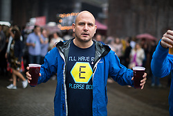 "© Licensed to London News Pictures . 01/07/2017 . Manchester , UK . A man wearing a Blockbusters "" E "" t-shirt in reference to the rave drug Ecstasy . Crowds enjoying the DJ sets ahead of the main act . Hacienda Classical play at the Castlefield Bowl as part of Sounds of the City , during the Manchester International Festival . A collaboration between DJs Mike Pickering and Graeme Park and the Manchester Camerata orchestra , Hacienda Classical reworks music by bands including the Happy Mondays and New Order and features Manchester musicians including Rowetta and Peter Hook . Photo credit : Joel Goodman/LNP"