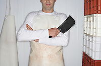 Butcher standing arms crossed  Holding Cleaver next to stack of crates mid section