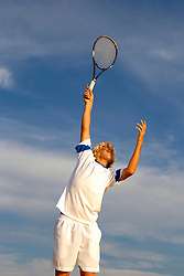 boy serving in a tennis game against the sky