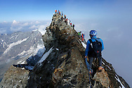 Alpinists on the summit of Matterhorn.<br /> <br /> &ldquo;Matterhorn 150 years Cervino&rdquo; - The year 2015 is the 150th Anniversary of the first ascent by Edward Whymper from the Swiss side (14th July) and by Jean Antoine Carrel from the Italian side on the 17th July 1865.<br /> <br /> On 17th July 2015 a friendship convention was signed by the members of Swiss, French, British and Italian climbing teams. A ceremony was held at the summit in honour of the mountain.