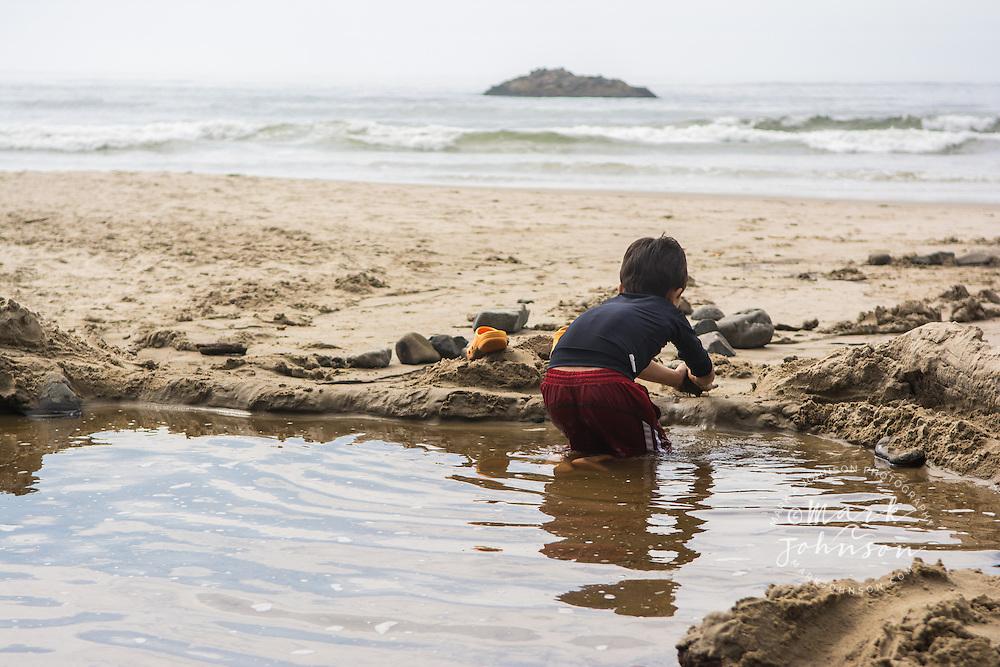 Boy building a sand castle at the beach on the Oregon coast, USA