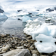 Blocks of Antarctic sea ice washed ashore on the rocky beach at Cuverville Island on the Antarctic Peninsula.