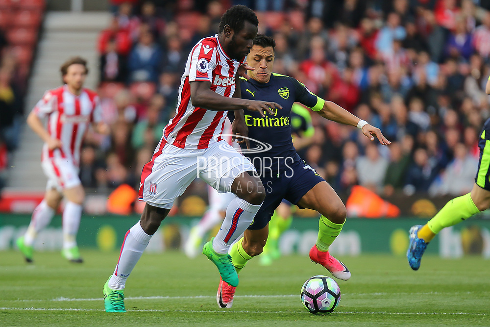 Stoke City forward Mame Biram Diouf and Arsenal forward Alexis Sanchez challenge for the ball during the Premier League match between Stoke City and Arsenal at the Bet365 Stadium, Stoke-on-Trent, England on 13 May 2017. Photo by Aaron  Lupton.