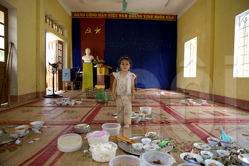 Portrait of a little vietnamese girl standing in the center of a very messy area full of wasted food. After the meal's party bowls and dishes lie around. Luc Yen, yen bai province, Vietnam, Asia.