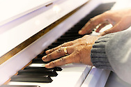 Close-up of Booker T Gibson's hands as he plays piano at Northport VA medical Center, on Dec. 19, 2011. Light vignette.