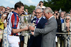 Audi England captain LUKE TOMLINSON receives the Westchester Cup from HRH The PRINCE OF WALES with JON ZAMMETT at the Audi International Polo at Guards Polo Windsor Great Park, Egham, Surrey on 28th July 2013.