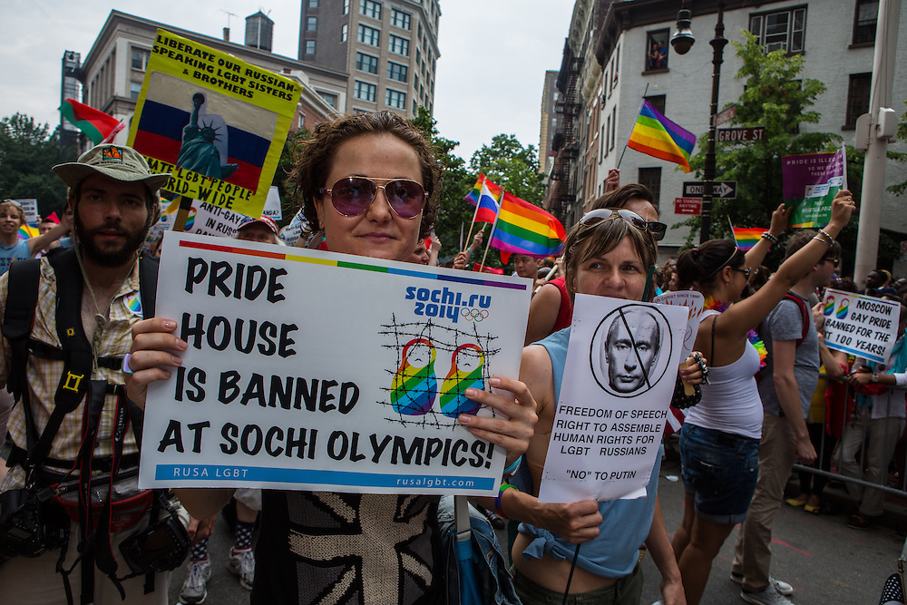 Marchers from RUSA LGBT, a Russian-speaking association, carry signs protesting the banning of a Pride House at the forthcoming Sochi Olympic games.