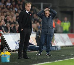 Crystal Palace Manager, Neil Warnock holds his hands oh his head looking dejected with Swansea City Manager, Garry Monk in the foreground. - Photo mandatory by-line: Alex James/JMP - Mobile: 07966 386802 - 29/11/2014 - Sport - Football - Swansea -  - Swansea v Crystal palace  - Barclays Premier League