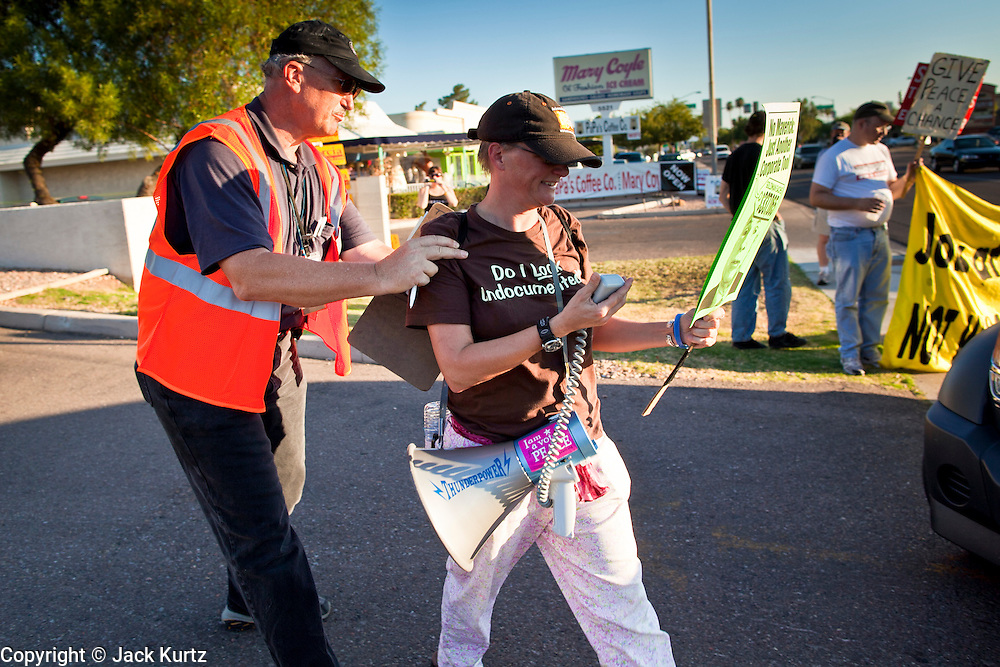26 SEPTEMBER 2010 - PHOENIX, AZ: A security guard escorts Liz Hourican off the property of KTVK TV in Phoenix after she tried to approach Sen John McCain during a picket against the Senator Sunday. About 200 people demonstrated and picketed against Arizona Republican Senator John McCain at the studios of KTVK TV in Phoenix, Sunday, Sept 26. They picketed the TV station because McCain was debating his opponents there. They were demonstrating against McCain's positions on the war in Afghanistan, Don't Ask Don't Tell (Gays in the military) and the DREAM Act (for immigrant rights). PHOTO BY JACK KURTZ