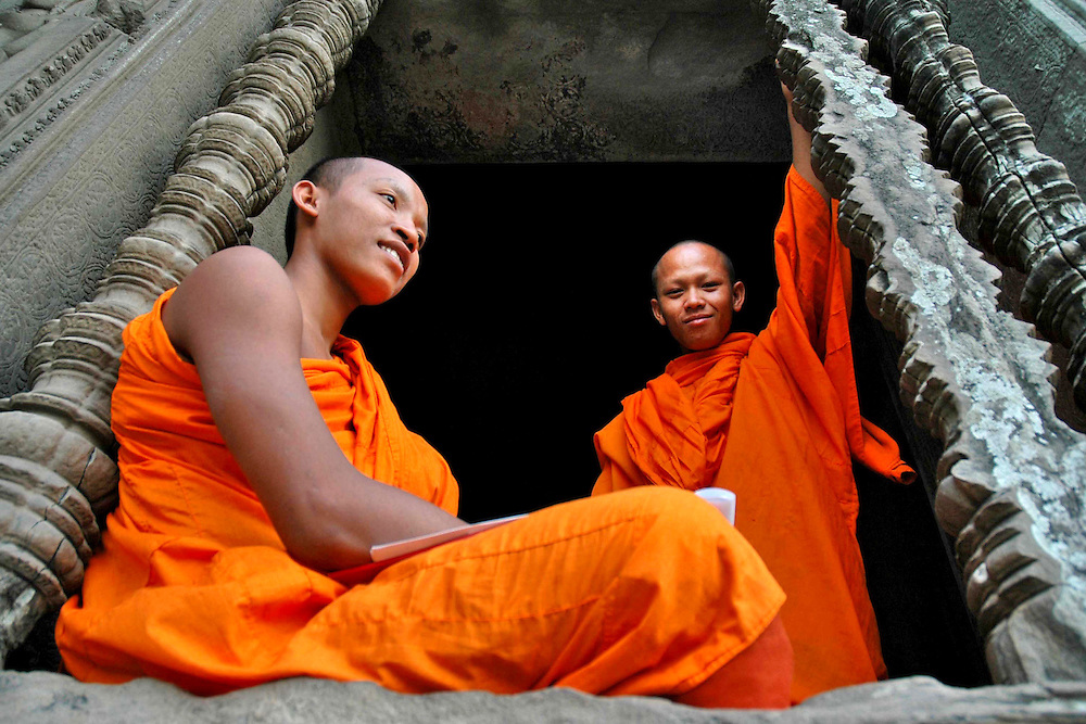 These two Cambodian Buddhist Monks were sitting in the interior of the Angkor Wat temple complex, a massive three-tiered pyramid crowned by five lotus-like towers rising 65 meters from ground level. <br /> <br /> Angkor Wat, the world's largest single religious monument, built for the king Suryavarman II in the early 12th century as his state temple and capital city.  <br /> <br /> The ruins of Angkor, a UNESCO World Heritage Site with temples numbering over 1000, are hidden amongst forests and farmland to the north of the Tonle Sap Lake outside the modern city of Siem Reap, Cambodia. <br /> <br /> Angkor Wat has remained a significant religious centre since its foundation--first Hindu, dedicated to Vishnu, then Buddhist. Quite a few of the temples at Angkor have been restored and represent a significant site of Khmer architecture.  Angkor Wat has become a symbol of Cambodia, appearing on its national flag and is worthy of all it's attention.