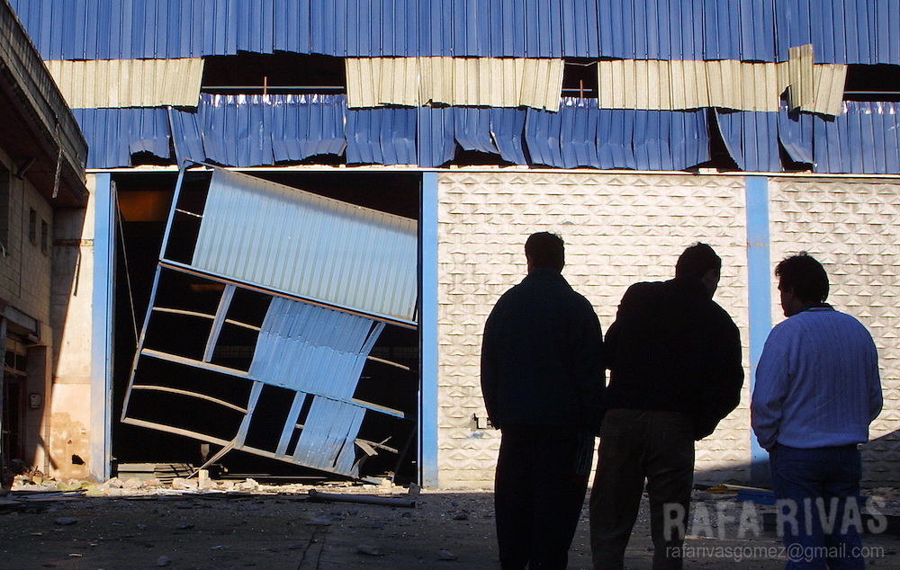 Three men look at a company building in the Basque village of Arrigorriaga, north of Spain, damaged by the explotion of a bomb planted by Basque separatist terrorist group ETA, on December 1, 2001. Photo Rafa RIVAS