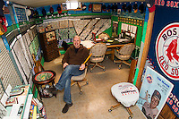"Bill Colby sits in his ""Fenway Park"" room filled with the history of American Baseball.  (Karen Bobotas/for the Laconia Daily Sun)"