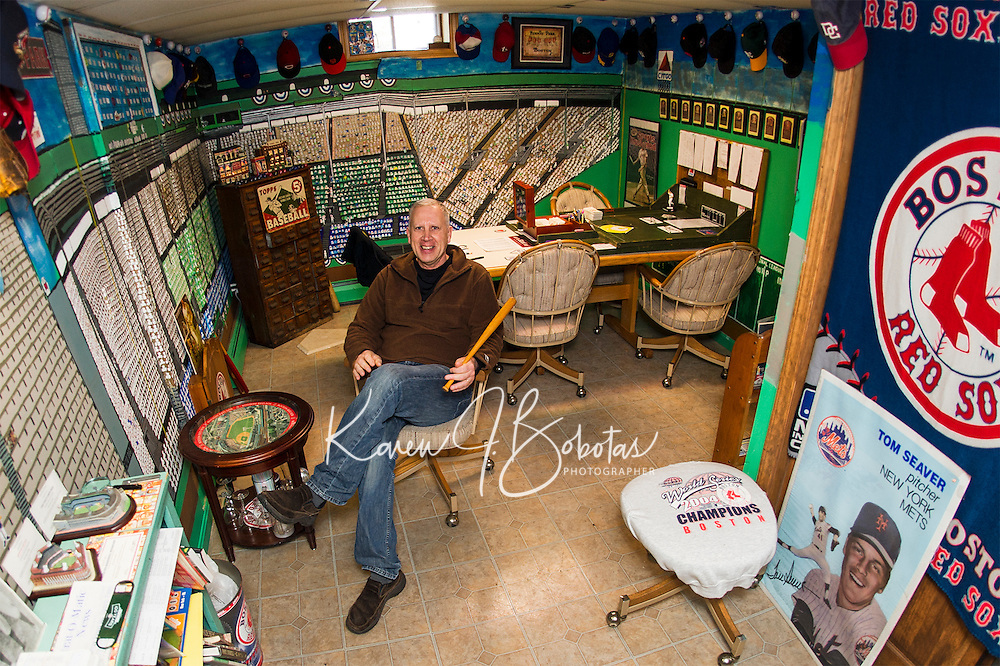 """Bill Colby sits in his """"Fenway Park"""" room filled with the history of American Baseball.  (Karen Bobotas/for the Laconia Daily Sun)"""