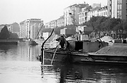 A worker pushes with a pole a barge for the transport of sand at the dock of the Naviglio Milan, April 1970. In the background the sand hoppers. Barges carry sand from Ticino river. © Carlo Cerchioli..Operaio spinge con una pertica un barcone per il trasporto della sabbia alla Darsena del Naviglio, Milano, aprile 1970. Sullo sfondo le tramoggie della sabbia. I barconi portano la sabbia dal Ticino.