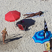 Sunbathers on Praia de Copacabana. Copacabana beach, one of the world's most famous urban beaches. The beach and hotel strip stretches for 1.5 miles (4km) from the Morro do Leme at the Northern end, to Arpoador. Copacabana beach, Rio de Janeiro,  Brazil. 21st July 2010. Photo Tim Clayton..