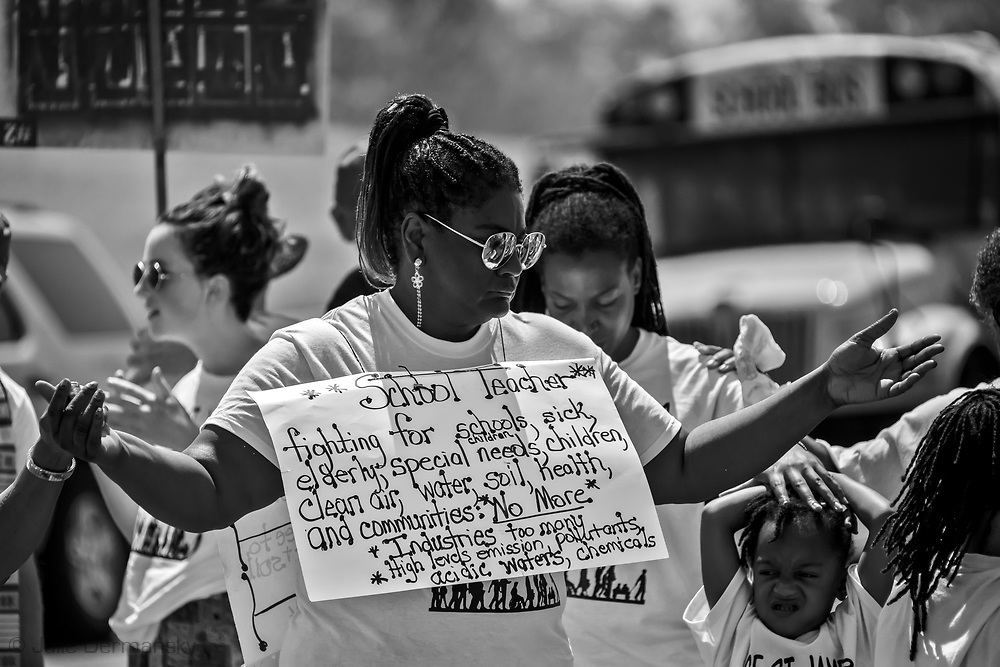 "Stephanie Cooper, the Vice President of Rise St. James  holding a sign in Welcome  Louisaina on the third day of a five day march through Louisiana's 'Cancer Alley' .. The march, held by the Coalition Against Death Alley. The Coalition Against Death Alley (CADA), is a group of Louisiana-based residents and members of various local and state organizations, is calling for a stop to the construction of new petrochemical plants and the passing of stricter regulations on existing industry in the area that include the groups RISE St. James, Justice and Beyond, the Louisiana Bucket Brigade, 350 New Orleans, and the Concerned Citizens of St. John. Louisiana's Cancer Alley, an 80-mile stretch along the Mississippi River, is also known as the ""Petrochemical Corridor,"" where there are over 100 petrochemical plants and refineries ."