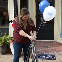 Sarah Stewart of the Downtown Main St. Association ties a Shop Small balloon to open sign for Swirlz in Downtown Tupelo Saturday