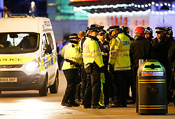 """© Licensed to London News Pictures. 24/02/2016. London, UK. Police in riot gear form a screen as a man is placed in to a van at the scene of a """"hostage situation"""" at Bella Italia restaurant in Leicester Square, London where a man claiming to be in possession of a knife is holding a woman against her will. Metropolitan Police reported the incident is not terrorist-related. Photo credit: Tolga Akmen/LNP"""