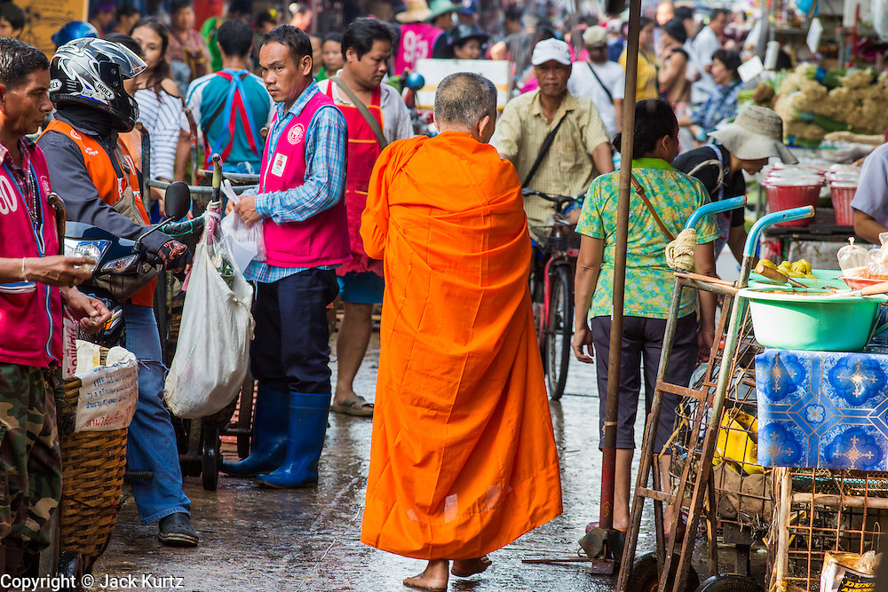 "26 SEPTEMBER 2012 - BANGKOK, THAILAND:  A Buddhist monk walks through the crowd in Khlong Toey Market in Bangkok. Khlong Toey (also called Khlong Toei) Market is one of the largest ""wet markets"" in Thailand. The market is located in the midst of one of Bangkok's largest slum areas and close to the city's original deep water port. Thousands of people live in the neighboring slum area. Thousands more shop in the sprawling market for fresh fruits and vegetables as well meat, fish and poultry.    PHOTO BY JACK KURTZ"