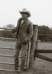 rugged cowboy outdoors by a gate on a ranch