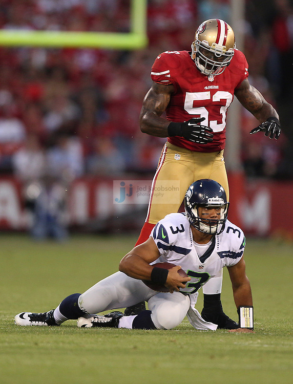Seattle Seahawks quarterback Russell Wilson (3) is tackled by San Francisco 49ers linebacker NaVorro Bowman (53) on Thursday, Oct. 18, 2012 at Candlestick Park in San Francisco. (AP Photo/Jed Jacobsohn)