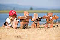 A yound builder creates Inukshuk's from bricks found on the Sidney Spit Marine Park near Sidney.  Southern Vancouver Island, British Columbia, Canada