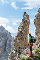 A male photographer as seen on a sunny Summer day photographing the Dolomites mountains from one versant close to Misurina village, South Tirol, Italy.