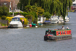 A couple cruise past the riverside homes at Weybridge in Surrey, July 03 2019.