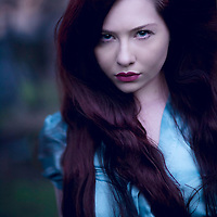 Young woman with long red hair blowing in wind wearing a blue blouse standing alone outdoors looking at camera