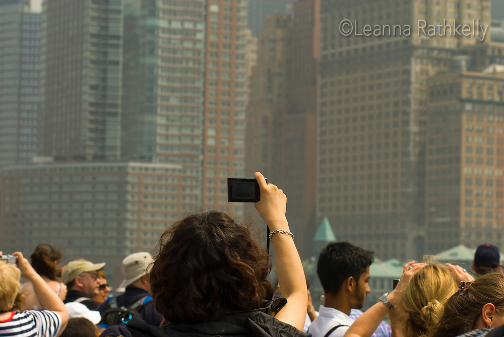 A tourist takes a photo of the Manhattan skyline from the boat to Liberty Island,  in New York City, NY USA