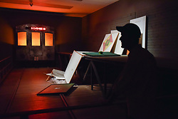 """© Licensed to London News Pictures. 17/10/2017. London, UK. A staff member views the installation called """"Not Everyone Will Be Taken Into The Future"""", 2001, at a preview of """"Not Everyone Will Be Taken Into The Future"""", the first UK exhibition by Russian artists Ilya and Emilia Kabakov.  The exhibition coincides with the 100th anniversary of the 1917 Russian Revolution and shows the couple's large scale installations and conceptual art.  Held at Tate Modern, the show runs 18 October to 28 January 2018. Photo credit : Stephen Chung/LNP"""
