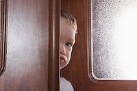 Young boy peeks round wooden door frame