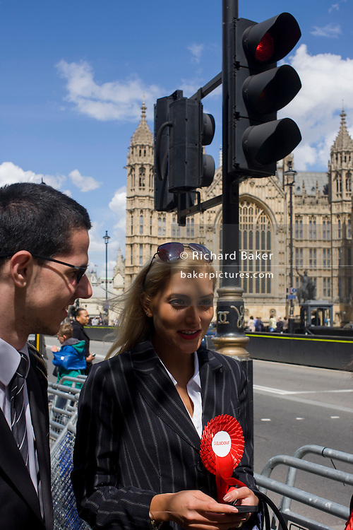 A Labour party supporter beneath a red traffic light, outside Parliament in Westminster, London.