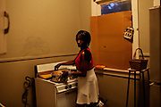 Vicki Wooten cooks dinner for her three children in Baptist Town, Mississippi on Wednesday, April 21, 2010. Her husband, a four-time convicted felon, is currently serving time in prison for running guns. Vicki and her children were evicted a few months later for not being able to pay their rent.