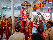 05 OCTOBER 2014 - GEORGE TOWN, PENANG, MALAYSIA: Men carry the deity to a waiting cart before a procession honoring Durga in George Town during the Navratri procession. Navratri is a festival dedicated to the worship of the Hindu deity Durga, the most popular incarnation of Devi and one of the main forms of the Goddess Shakti in the Hindu pantheon. The word Navaratri means 'nine nights' in Sanskrit, nava meaning nine and ratri meaning nights. During these nine nights and ten days, nine forms of Shakti/Devi are worshiped.   PHOTO BY JACK KURTZ