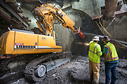 A large excavator fittedwith a jackhammer has begun breaking through the slurry wall at the station cavern entrance archway.  Once this work is complete, excavation of the station cavern will begin in phases.