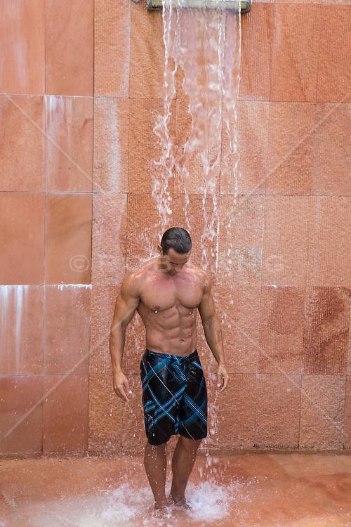 man enjoying time in a man made waterfall in Bermuda