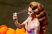 Een deelnemer spuit nog wat haarlak in het haar.. In Utrecht wordt voor de derde keer de Utrecht Canal Pride gehouden. Ruim veertig boten varen door de Utrechtse grachten om te vieren dat je kunt zijn wie je wilt zijn en kunt houden van je wie je wil. <br /> <br /> In Utrecht over 40 boats sail at the canals for the third Utrecht Canal Pride, the parade to celebrate that you can be who you want to be and to love who you want to love.