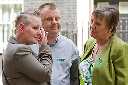 © Licensed to London News Pictures. 16/07/2013. London, UK. Julie Hilling, MP for Bolton West (R) and Shirley (L) and Michael Anderson (C), the parents of Jade Anderson, who was mauled to death by dogs, stand in Downing Street after handing in a petition to Number 10 Downing Street today (16/07/2013) calling on the Government to take more action on dangerous dogs. Photo credit: Matt Cetti-Roberts/LNP
